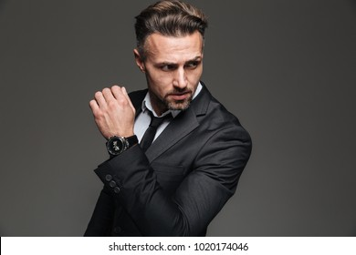 Portrait of handsome serious businessman in black suit looking aside with fancy wrist watch isolated over white background