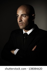 Portrait of handsome serious man wearing black stylish suit isolated on dark background, successful businessman