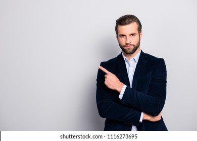 Portrait of handsome serious strict concentrated focused wealthy masculine virile elegant attractive banker with modern haircut pointing on empty blank space isolated on gray background copyspace