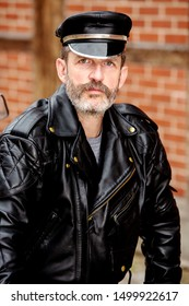 portrait of handsome sexy bearded man dressed in black leather