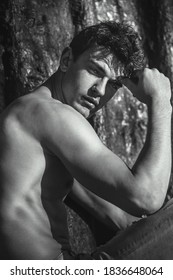 Portrait of handsome sexy male model posing shirtless and staring at the camera. Black and white