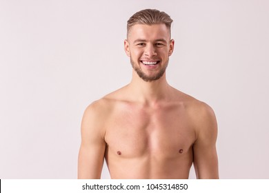 Portrait of handsome shirtless man looking to camera and smiling while standing isolated on white background. Young bearded hipster standing naked. Muscular and masculine man. Perfect men's beauty