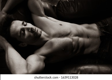 Portrait of handsome shirtless muscular man with beard and sixpack abs lying in leather armchair, sleeping.