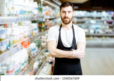 Portrait of a handsome shop worker or milkman standing near the selves with dairy products in the supermarket