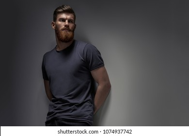 Portrait of handsome single bearded young man with serious expression in gray short sleeve shirt looking over gray background with copy space