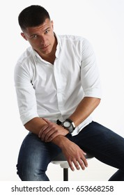 Portrait of a handsome smile young man in a white shirt, sitting on a chair and looking at the camera