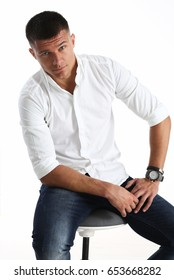Portrait of a handsome smile young man in a white shirt, sitting on a chair, looking serious