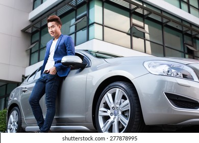 Portrait of an handsome smiling asian business man with his car and white shirt and blue coat