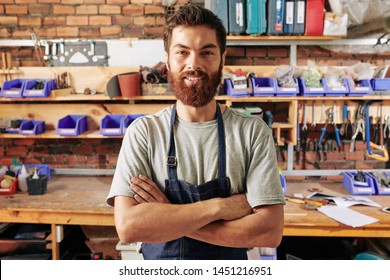 Portrait of handsome smiling bearded carpenter standing with his arms crossed and looking at camera