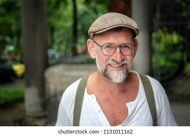 portrait of handsome smiling bearded man with hat and eyeglasses in his 50s
