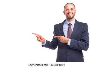 Portrait of handsome smiling business man pointing at copy space, isolated on a white background
