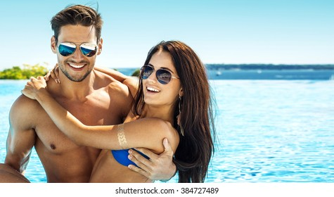 Portrait of handsome smiling couple having fun in swimming pool wearing sunglasses
