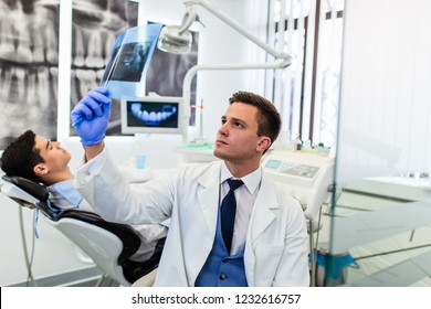 Portrait of handsome smiling dentist looking at x-ray image of his patient.