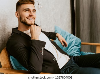 Portrait of handsome smiling hipster lumbersexual businessman model wearing casual black suit. Fashion stylish man posing sitting in chair in luxury interior. Thinking
