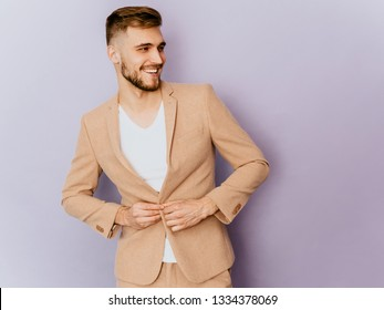 Portrait of handsome smiling hipster lumbersexual businessman model wearing casual beige suit. Fashion stylish man posing in studio