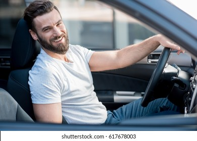 Portrait of a handsome smiling man dressed casual in white t-shirt sitting in the car in the city