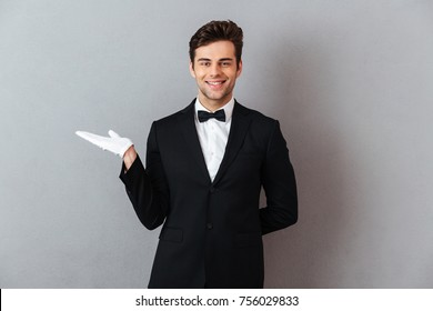 Portrait of a handsome smiling man dressed in tuxedo and gloves holding copy space on his palm isolated over gray background