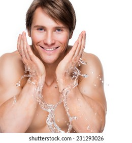 Portrait of a handsome smiling man washing his healthy face with water - isolated on white.