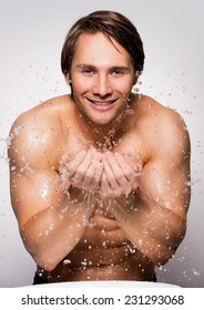 Portrait of a handsome smiling man washing his healthy face with water on gray background.