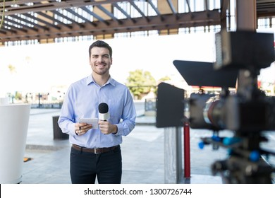 Portrait of handsome smiling newsman holding microphone and notepad in front of camera