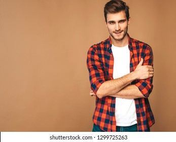 Portrait of handsome smiling stylish hipster lumbersexual businessman model dressed in red checkered shirt. Fashion man posing on golden background. Crossed arms