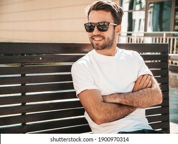 Portrait of handsome smiling stylish hipster lambersexual model.Man dressed in white T-shirt. Fashion male sitting at the bench in the street background in sunglasses. Crossed arms