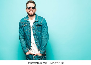 Portrait of handsome smiling stylish hipster lambersexual model.Man dressed in jacket and jeans. Fashion male posing near blue wall in studio in sunglasses