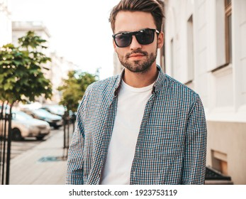 Portrait of handsome smiling stylish hipster lambersexual model.Man dressed in white T-shirt. Fashion male posing in the street in sunglasses