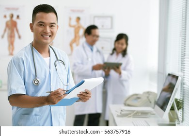 Portrait of handsome smiling Vietnamese doctor with folder looking at camera