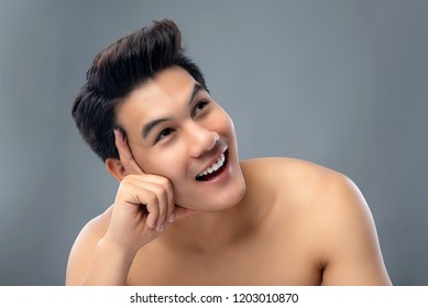 Portrait of handsome smiling young Asian man thinking and looking at space aside studio shot isolated on gray background