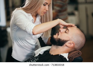 Portrait of handsome smiling young bearded caucasian man getting trendy haircut in modern barbershop. Attractive barber girl working, serving client, doing haircut using shaver.