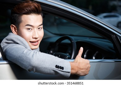 Portrait of an handsome smiling young business man with his car and gray suite