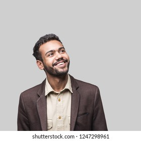 Portrait of handsome smiling young man looking up. Laughing joyful cheerful men studio shot. Isolated on gray background