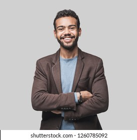 Portrait of handsome smiling young man with folded arms. Laughing joyful cheerful men with crossed hands studio shot. Isolated on gray background