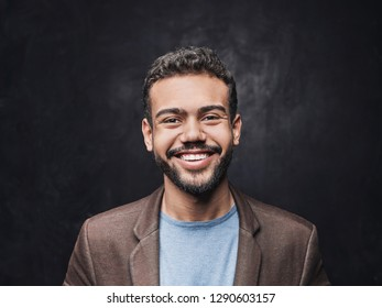 Portrait of handsome smiling young man. Laughing joyful cheerful men studio shot on black background