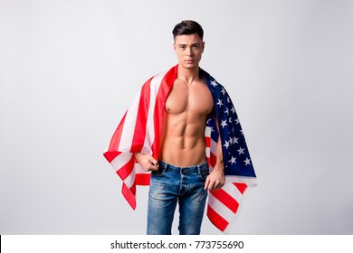Portrait of handsome sportive confident athletic nude guy wearing jeans, he is holding american flag on his shoulders and back, isolated on grey background, copy-space