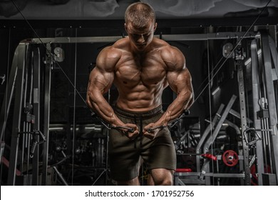 Portrait of handsome sporty man with naked muscular torso doing weight lifting