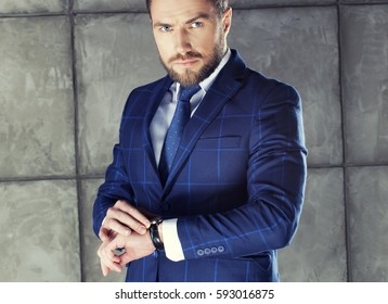 Portrait of handsome stylish bearded young man in elegant blue suit with vest and tie, perfect hair style checking time on watch. Toned