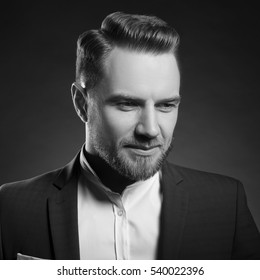 Portrait of handsome stylish caucasian young man in elegant blue suit with perfect hair style. Black and white