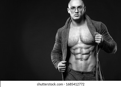 Portrait of handsome stylish man bodybuilder with naked torso in elegant suit. Guy in glasses. Black and white photo