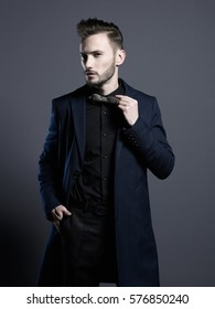 Portrait of handsome stylish man in elegant autumn coat. Young beautiful man in black coat. Beautiful male wear. Man with stylish haircut. Modern fashion. Elegant men's style. New fashionable look.