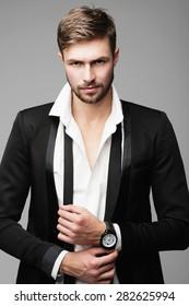 Porträt eines hübschen stylischen Mannes in einem Anzug in einem Studio auf grauem Hintergrund