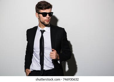 Portrait of a handsome stylish man in suit and tie posing while standing and looking away isolated over gray background