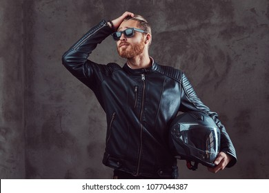 Portrait of a handsome stylish redhead biker in a black leather jacket and sunglasses, holds motorcycle helmet, posing in a studio.