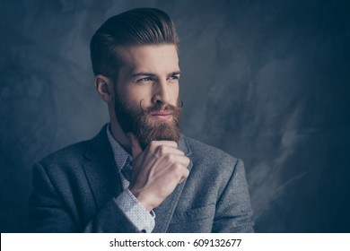 portrait of handsome stylish young man with mustache, beard and beautiful hairstyle keep calm and think while hold beard and chin with hands.