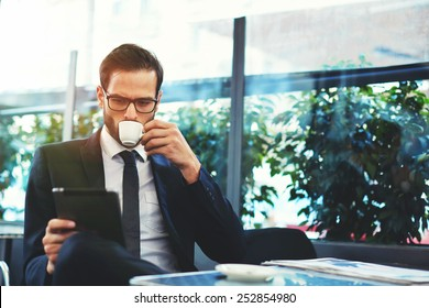 Portrait of handsome successful man drink coffee and look to the digital tablet screen sitting in coffee shop, business man having breakfast sitting on beautiful terrace with plants