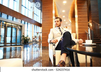 Portrait of handsome successful man drink coffee sitting in coffee shop, business man having breakfast at hotel lobby