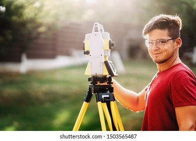 portrait of handsome surveyor working with total station with coordinates, cartography industry details