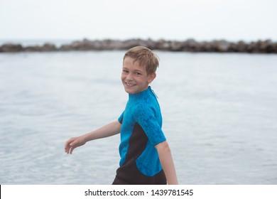 Portrait of handsome teen boy running in neoprene swimsuit in Baltic sea