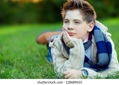 portrait of handsome teenager on green grass